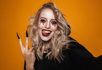 Joyful witch woman wearing black costume and halloween makeup smiling at the camera, isolated over yellow background