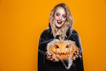 Scary woman wearing black costume and halloween makeup holding carved pumpkin, isolated over yellow background Fototapete