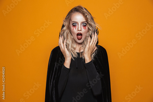 Scary woman wearing black costume and halloween makeup looking at the camera, isolated over yellow background