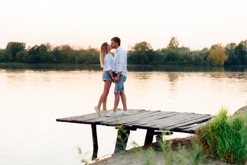 Young beautiful enamored couple walking outdoors in summer at sunset
