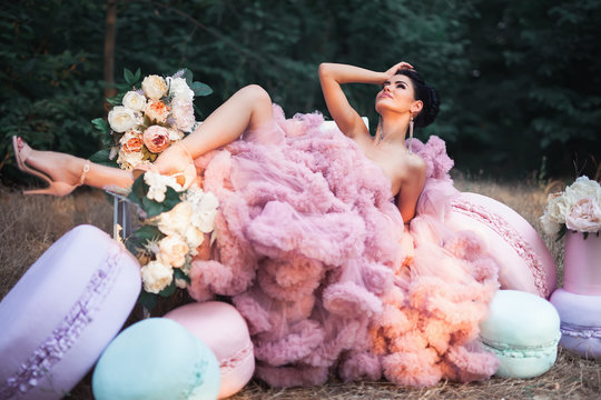 Fashion sexy woman dressed in pink stunning dress surrounded of French Macarons