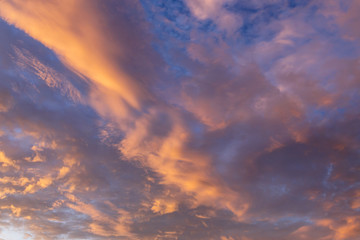 Abstract background with a texture of clouds at sunset. Heavenly landscape. A beautiful morning blue sky painted in the sun in bright red and orange colors