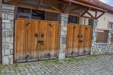 Wooden gates with stone columns. The design is vintage style