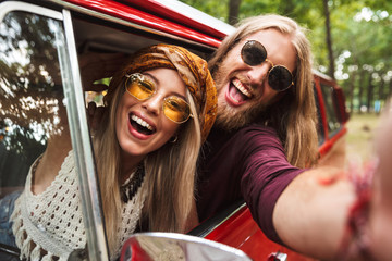 Photo of young hipsters man and woman smiling, and sitting in retro minivan in forest