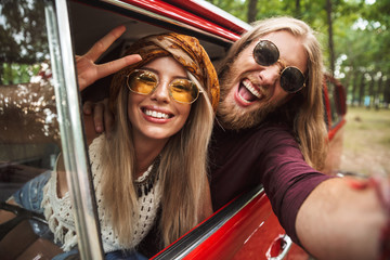 Photo of european hippie couple smiling, and showing peace sign while driving retro minivan in forest