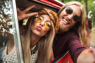 Photo of kind hippie couple smiling, and showing peace sign while driving retro minivan in forest