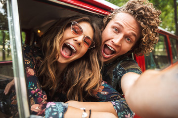 Photo of happy hippie couple smiling, and showing peace sign while driving retro minivan in forest
