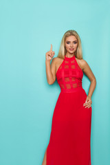 Sexy Blond Woman In Red Dress Is Pointing Up