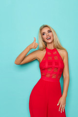 Sexy Blond Woman In Red Dress Is Showing Thumb Up, Looking Away And Smiling