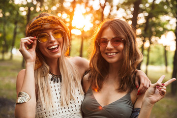 Photo of two happy hippie women, smiling and hugging each other while walking in forest