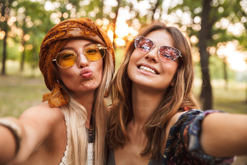 Photo of two european hippie women, smiling and taking selfie while walking in forest