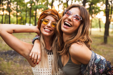 Photo of two young hippie girls, smiling and hugging each other while walking in forest