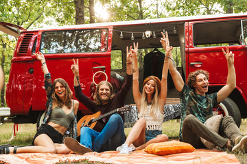 Group of friends hippies men and women rejoicing, and sitting near vintage minivan into the nature