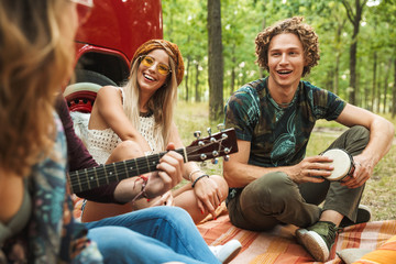 Group of friends hipsters men and women laughing, and playing guitar near vintage minivan in forest