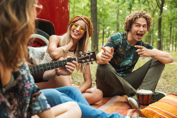 Group of smiling people hipsters men and women laughing, and sitting near vintage minivan in forest