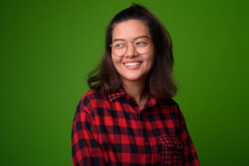 Young beautiful Asian hipster woman wearing eyeglasses and red checkered shirt