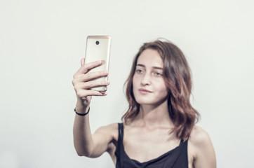 Beautiful young girl holding a phone. Makes photos, selfies