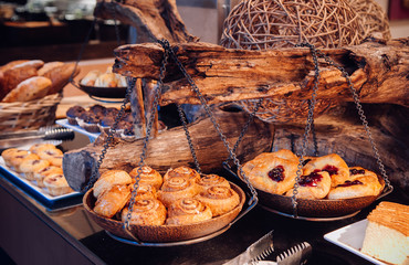 Cinnamon roll and cherry danish pastry on wooden tray hanging on wood log
