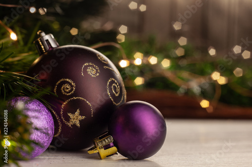 christmas toy purple ball with a gold pattern next to small purple balls on a light - Small Purple Christmas Tree
