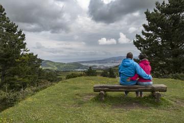 Pareja sentada en banco mirando el paisaje