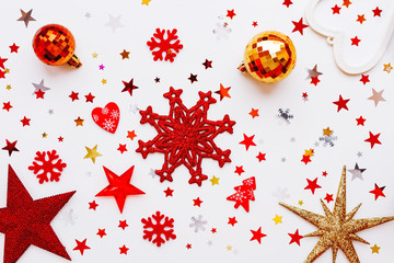 Christmas and New Year holiday background with decorations and light bulbs. Red and golden hearts, shiny balls, felt snowflakes and star confetti. Flat lay, top view.