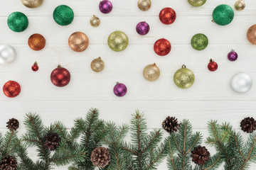 beautiful shiny colorful christmas balls and fir twigs with pine cones on white wooden background