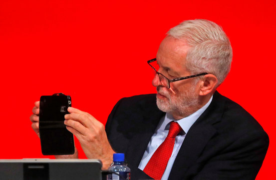 Britain's Labour Party leader Jeremy Corbyn uses his mobile phone whilst listening to Shadow Secretary of State for Business, Energy and Industrial Strategy Rebecca Long-Bailey, deliver her keynote speech at the annual Labour Party Conference in Liverpool