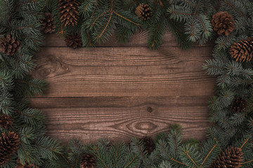 top view of beautiful evergreen coniferous branches and pine cones on wooden background