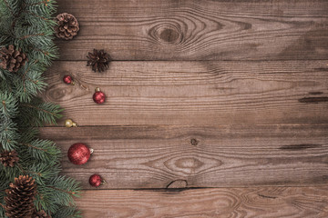 top view of shiny balls, coniferous twigs and pine cones on wooden background