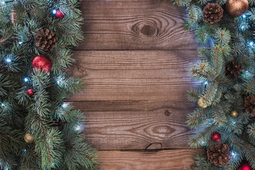 top view of coniferous twigs with shiny baubles, pine cones and illuminated garland, christmas background