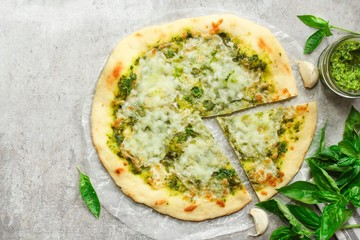 Homemade Pesto pizza sliced with fresh basil leaves top down view