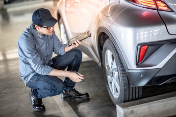 Young Asian auto mechanic holding digital tablet checking car wheel in auto service garage. Mechanical maintenance engineer working in automotive industry. Automobile servicing and repair concept