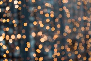 Christmas abstract background. Blurred golden garland blur bokeh, defocused pattern.