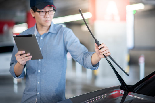 Young Asian auto mechanic holding digital tablet checking windshield wiper in auto service garage. Mechanical maintenance engineer working in automotive industry. Automobile servicing and repair