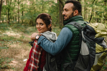smiling man hugging woman while hiking in forest together