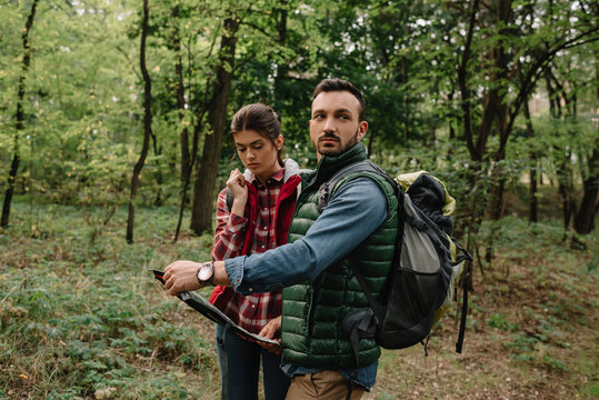 couple of travelers with map got lost in woods
