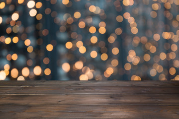 Blurred gold garland and wooden tabletop as foreground. Image for display or montage your christmas products.