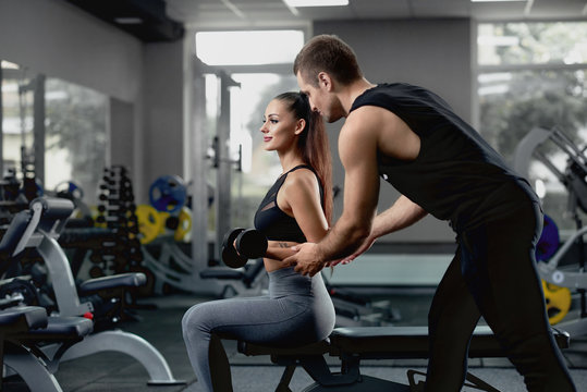 Handsome personal instructor helping his female client to training with dumbbells.