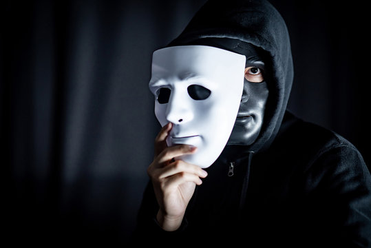 Mystery hoody man wearing black mask holding white mask. Anonymous social masking. Major depressive disorder or bipolar disorder. Halloween concept