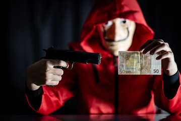 Mystery man wearing mask and red hoodie holding gun showing euro banknote in his hand. Anonymous thief or robber committing a robbery. Crime and violence concept