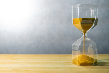 Gold sand running through the shape of modern hourglass on wooden table.Time passing and running out of time. Urgency countdown timer for business deadline concept