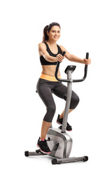 Young female riding a stationary bike