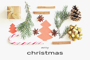 Merry Christmas greeting card. Gift box, ribbon, fir branches, cones, star anise, cinnamon, candy cane and paper christmas tree on white background with congratulation text