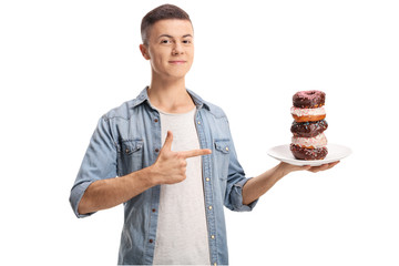 Teenage boy holding a pile of donuts on a plate and pointing with finger