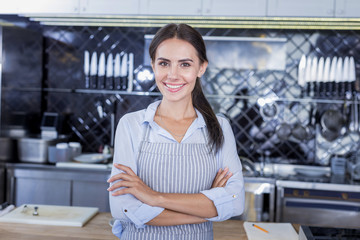 Wonderful smile. Beautiful attractive woman smiling while posing in the kitchen