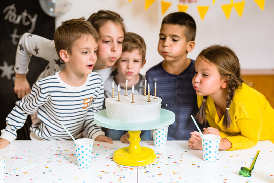 Kids blowing birthday cake candles