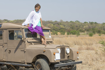 Woman with purple dress and vintage land rover.