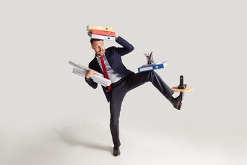 Fototapeta Young businessman in a suit juggling with office supplies in his office, isolated on white background. Conceptual collage with phone, folders. The business, office, work concept.