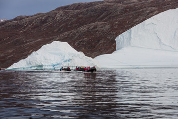 Foto op Aluminium Poolcirkel rubber dinghy cruising in front of massive Icebergs floating in the fjord scoresby sund, east Greenland