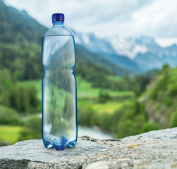 Fototapeten Wasser Bottle of water on the stone. Blurred snow mountains tops and green forests